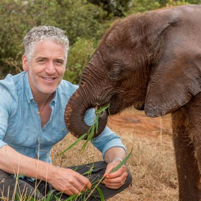 Gordon Buchanan wearing a pale blue shirt, crouched beside a brown elephant
