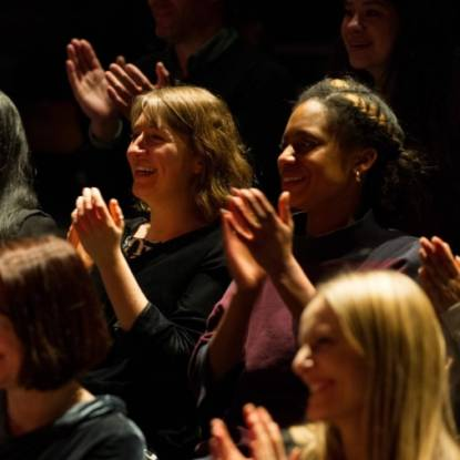 Colour photo of women smiling and applauding