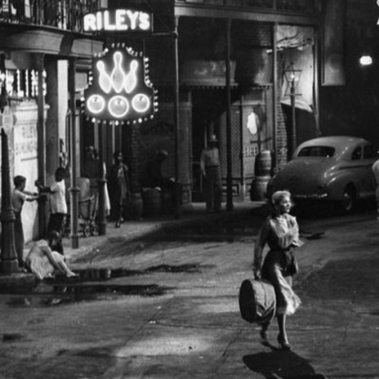 A black and white image of a woman in the street outside a jazz bar