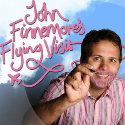 John Finnemore in front of a blue sky, writing the words John Finemore's Flying Visit in pink