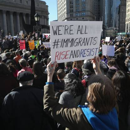 Colour photo of a crowd of people. A protest sign reads 'We're all immigrants'