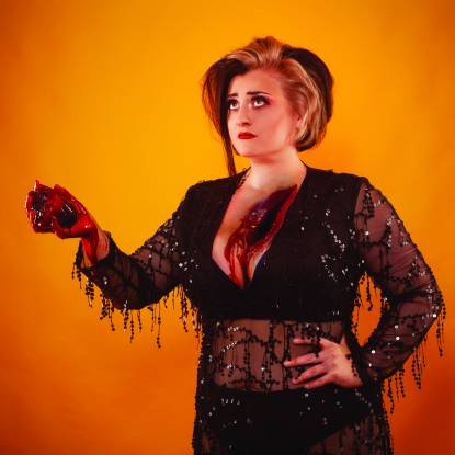 Kiri Pritchard-McLean wearing black lace holding a bloody heart which has been ripped out of her chest, in front of an orange background