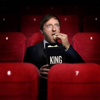 "Andrew Maxwell eating popcorn from a box reading ""King"""