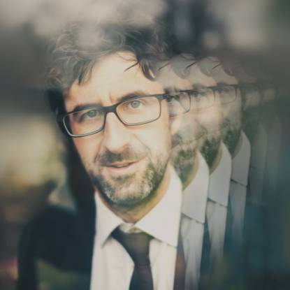 Mark Watson wearing glasses, reflected 4 times