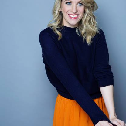 Rachel Parris wearing a navy blue jumper and an orange skirt, standing in front of a light blue background