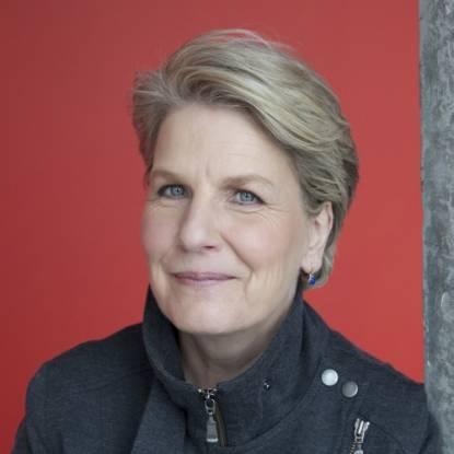Sandi Toskvig wearing a black jacket against a red background