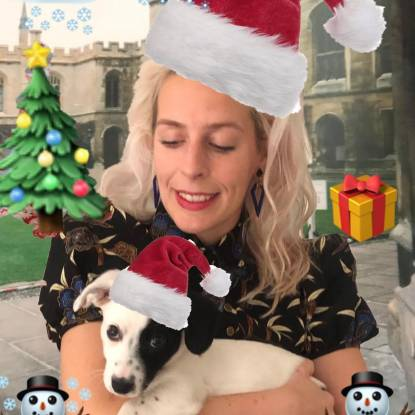 Sara Pascoe wearing a christmas hat holding a dog, also wearing a christmas hat