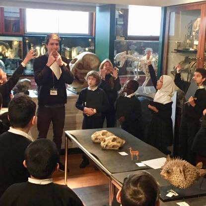 School children in a museum look at animal bones on a table