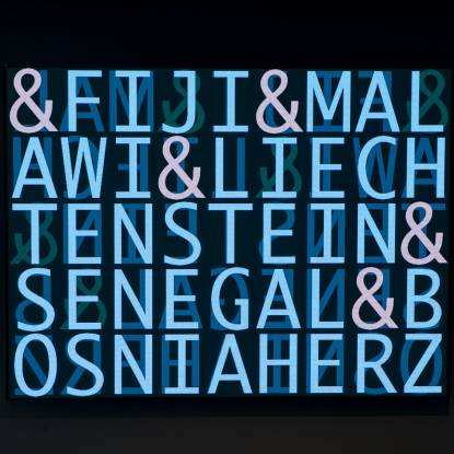 Colour photo showing a dark screen with bright blue neon letters spelling the names of different countries