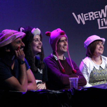 Four comedians at a table, one wearing a Werewolf hat