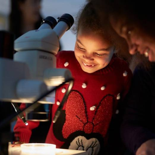 Little girl looking at microscope