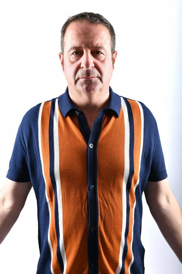 Mark Thomas standing in front of a white background