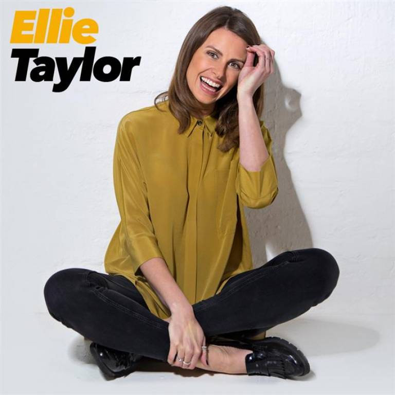 Ellie Taylor sat cross legged in front of a grey background