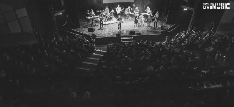 A black and white image of a band on stage and an audience watching