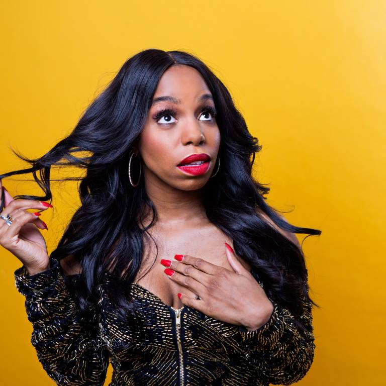 London Hughes dresses in black and gold, in front of a yellow background