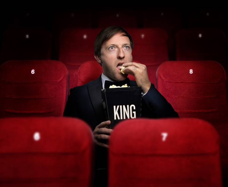 """Andrew Maxwell eating popcorn from a box reading """"King"""""""