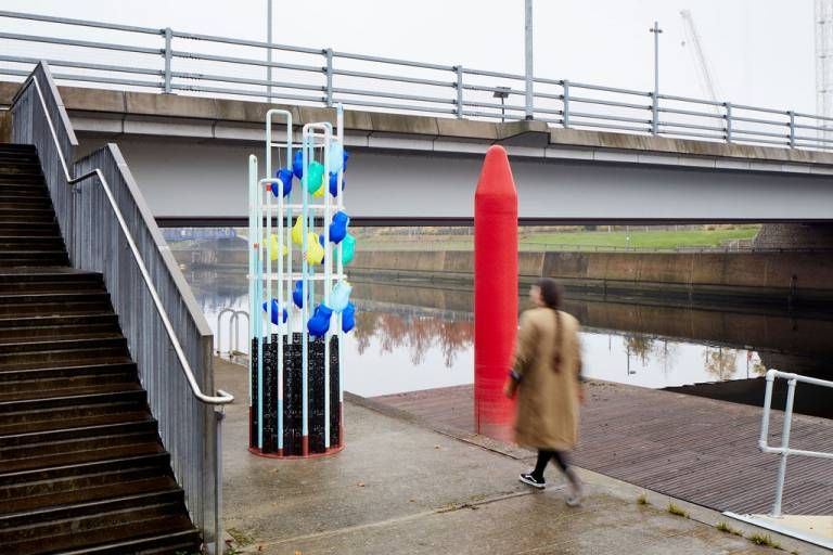 woman walks past cylindrical structure from which hand multicoloured jugs. She is on the bank of a river and walking towards a bridge.