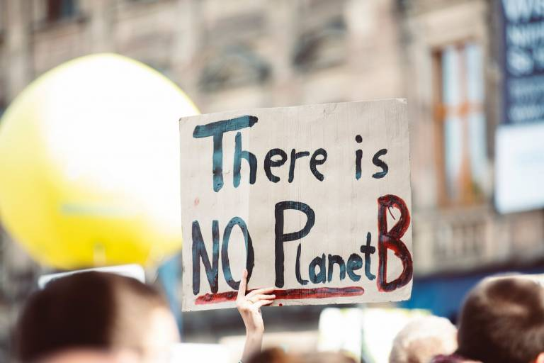 A protestor holds a sign reading There is No Planet B
