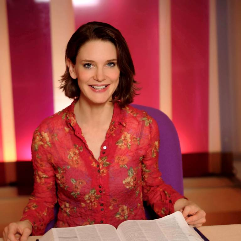 Susie Dent in a red floral shirt, holding an open dictionary