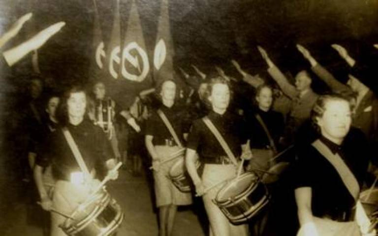 Sepia image of people marching and banging drums