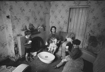 Black and white photo showing a woman sitting inside with children around her