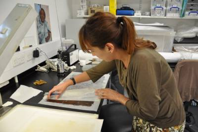 Image of papyrus conservator at work restroing a piece of papyrus