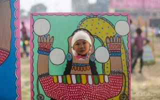 Photo of child's face peering through a cartoon cutout of a traditional character