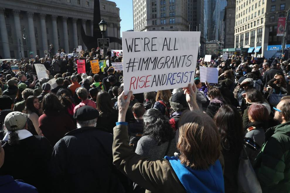 Colour photo of people protesting. A sign reads 'We're all immigrants'