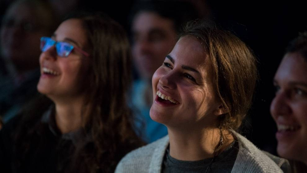 Photograph of audience smiling and laughing