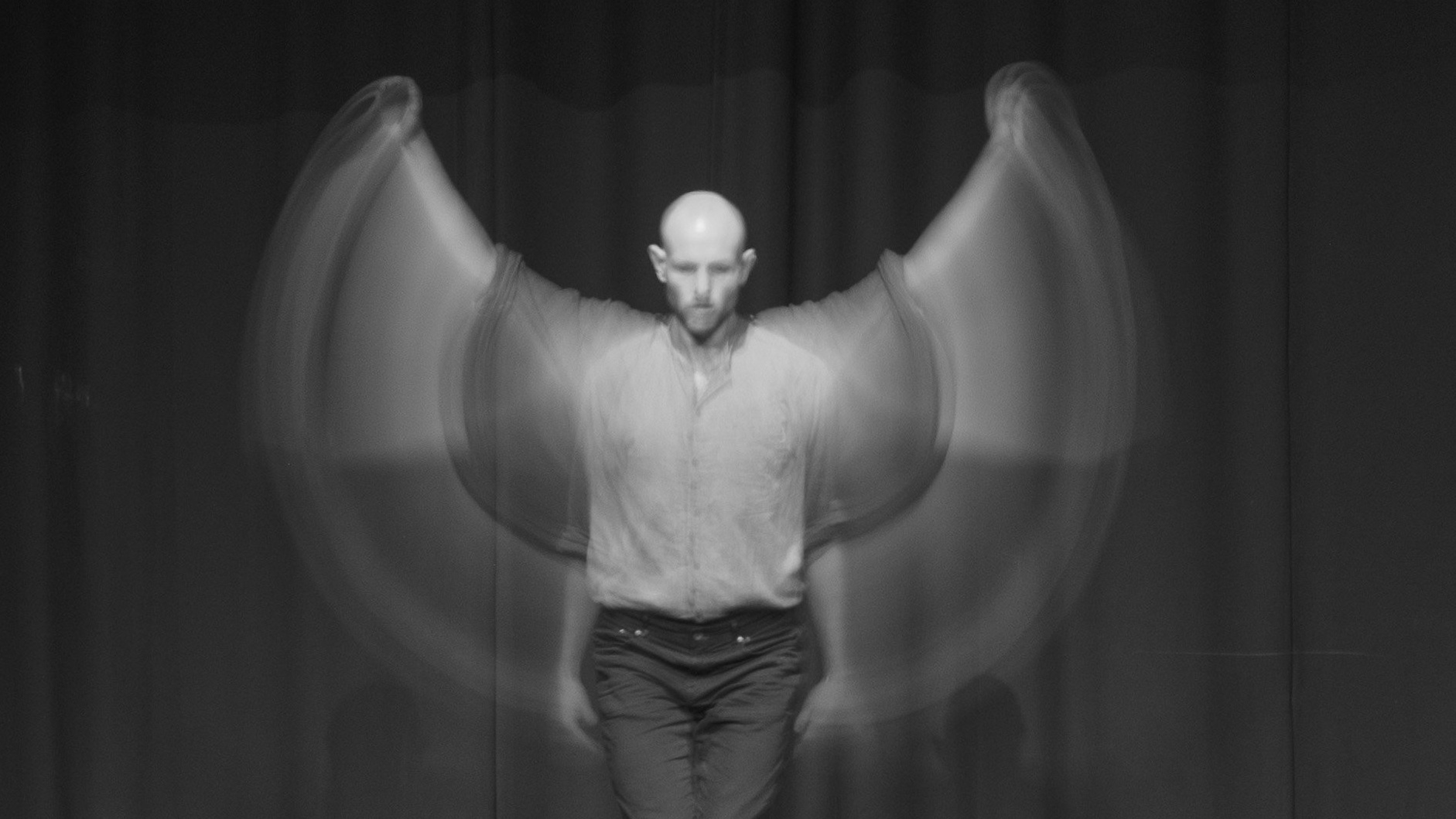Black and white photo of a man sttanding upright moving arms in a circle in front of him