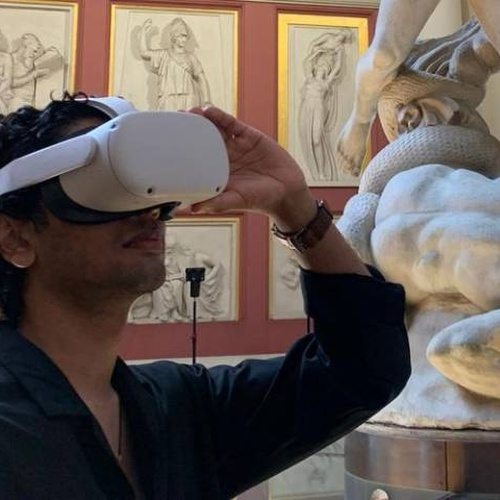 man wearing a virtual reality headset standing in an art gallery filled with classical sculptures