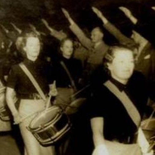 Sepia photograph showing women playing military-style drums with people making a Nazi salute in the background