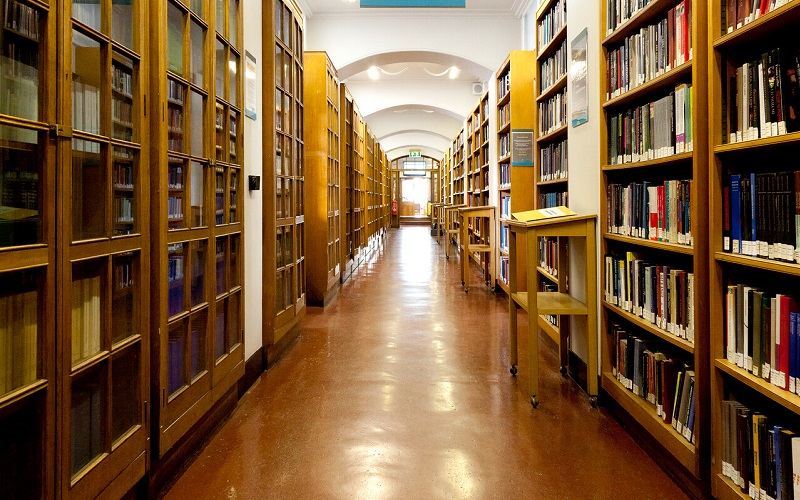 looking down a long corridor with rows of books either side