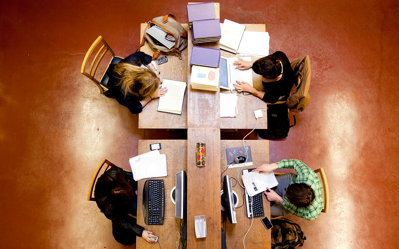 birdseye view of four students studying in the library