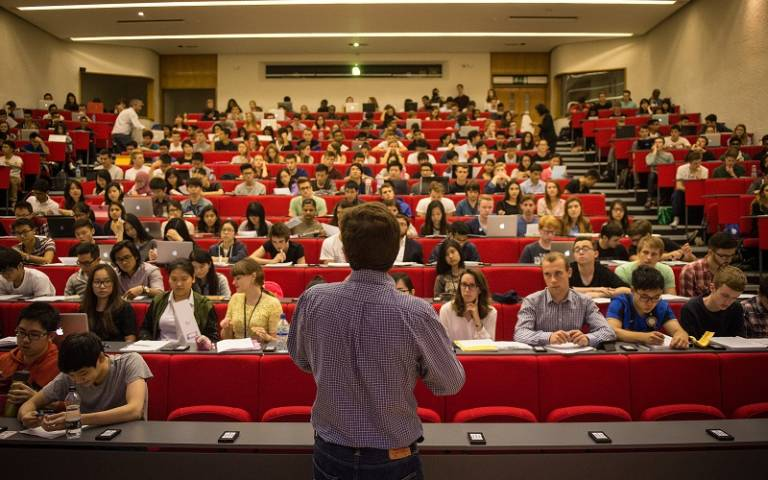 profile of lecturer speaking to a lecture hall of students