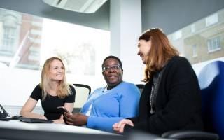 Staff sat around a desk chatting