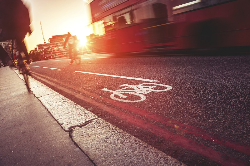 An image of two cyclists in a bicycle lane next to a bus, in front of a setting sun behind