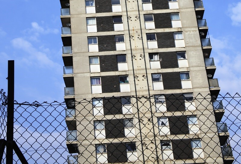 An image of a section of a tower block behind a chain link fence