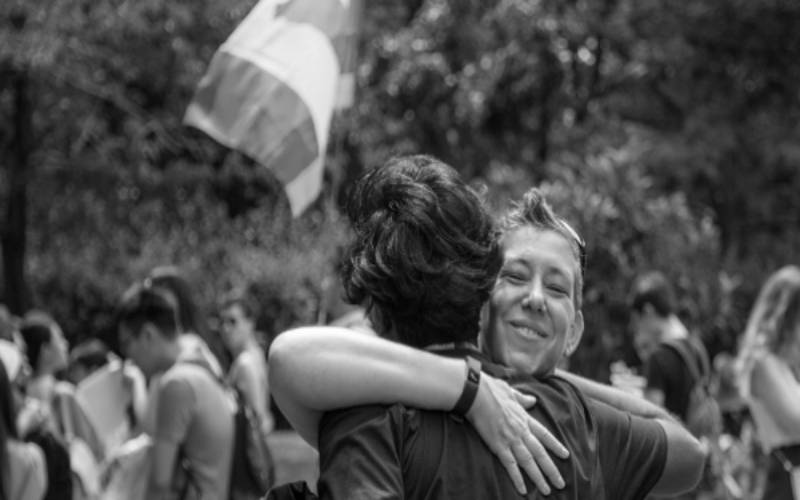 Two people embracing at an LGBTQ outdoor event