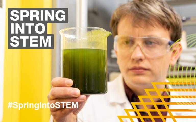 A man examines a jar of green algae