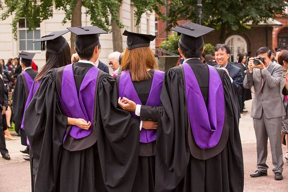 Students on graduation day in gowns backs to camera
