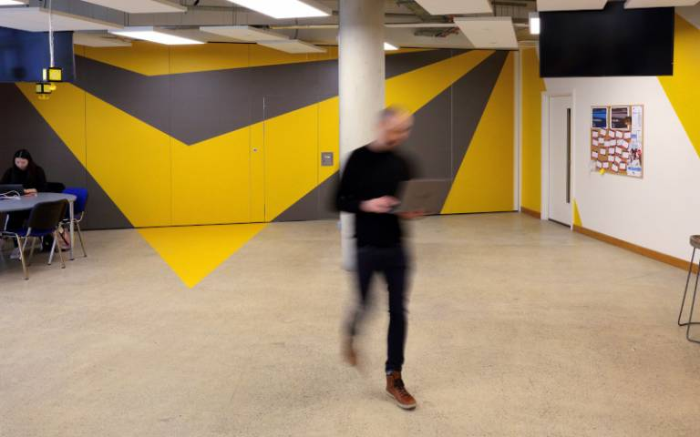 A person strides through the open plan space at BaseKX