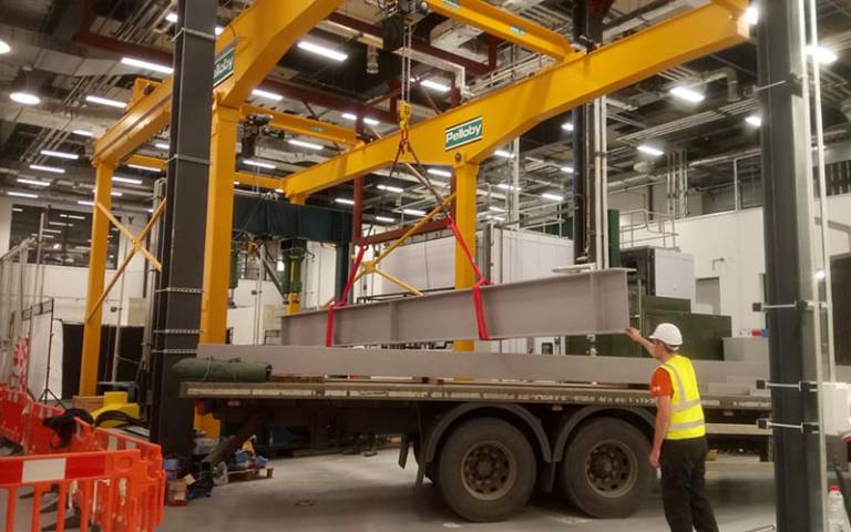 Crane lowering a heavy load onto a flatbed lorry within a large building