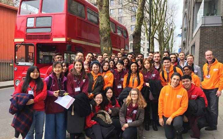 A group of UCL students standing in front of a red London bus, taking part in the London Venture Crawl 2019