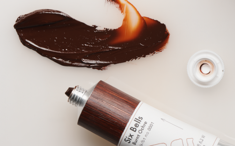 A smudge of brown paint, next to a tube labelled 'Six Bells Burnt Ochre'
