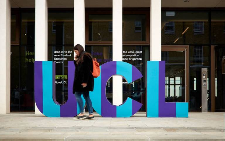 Student walking past a UCL building with giant letters spelling out UCL
