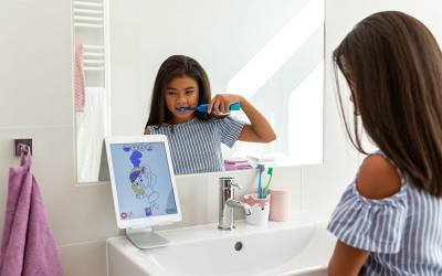 A child brushing their teeth in a bathroom looking at the Playbrush app on a tablet computer