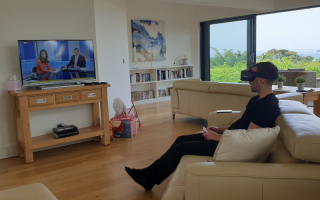 Person sitting on a sofa opposite a TV wearing a headset