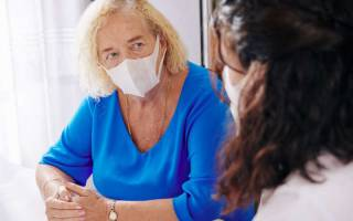Social care worker talking to a patient, both wearing face masks