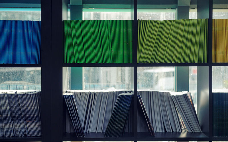 Green and blue files on a shelf